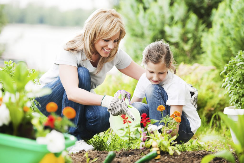 Front view of a mother and her daughter gardening.